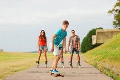 El grupo de adolescentes sonrientes con patina sobre ruedas Imagen de archivo libre de regalías