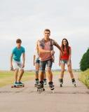El grupo de adolescentes sonrientes con patina sobre ruedas Foto de archivo