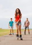 El grupo de adolescentes sonrientes con patina sobre ruedas Imágenes de archivo libres de regalías