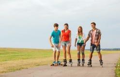 El grupo de adolescentes sonrientes con patina sobre ruedas Imagenes de archivo