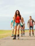 El grupo de adolescentes sonrientes con patina sobre ruedas Fotos de archivo