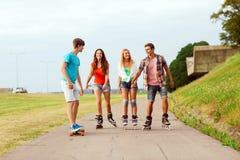 El grupo de adolescentes sonrientes con patina sobre ruedas Foto de archivo libre de regalías