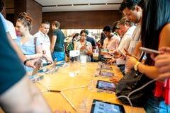 El grupo de adultos embroma a los clientes que prueban jugar en el último iPhone Imágenes de archivo libres de regalías