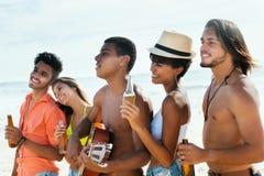 El grupo de adultos jovenes disfruta de vida en la playa Imagen de archivo libre de regalías