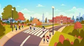 El grupo de alumnos que caminan en estudiantes de la raza de la mezcla del paso de peatones va a la calle de la travesía de escue Foto de archivo libre de regalías