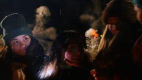 El grupo de amigos en mujer joven del bosque del invierno cuenta a sus amigos una historia asustadiza almacen de metraje de vídeo
