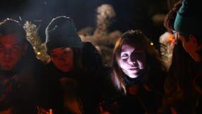 El grupo de amigos en mujer joven del bosque del invierno cuenta a sus amigos una historia asustadiza y consiguen asustados almacen de metraje de vídeo