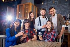 El grupo de amigos en una reunión con los vidrios ríe y sonríe Fotografía de archivo libre de regalías