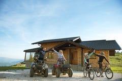 El grupo de amigos es alrededor comenzar aventura en las bicis de montaña y las bicis del patio del atv delante de la casa de la  Fotografía de archivo libre de regalías