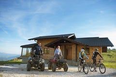 El grupo de amigos es alrededor comenzar aventura en las bicis de montaña y las bicis del patio del atv delante de la casa de la  Imagen de archivo libre de regalías