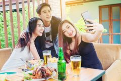 El grupo de amigos está tomando el selfie y comiendo la comida sea enj feliz Imagen de archivo