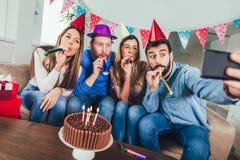 El grupo de amigos felices que celebran cumpleaños en casa hace la foto del selfie imagen de archivo libre de regalías