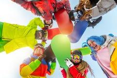 El grupo de amigos felices se coloca en círculo con las snowboard Imagenes de archivo