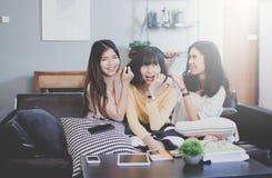 El grupo de amigos femeninos adolescentes asiáticos jovenes en cafetería, tiene la diversión y risa junto Imagenes de archivo