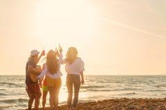 El grupo de amigos juega en la playa foto de archivo