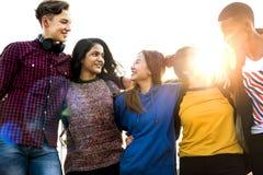 El grupo de amigos de la escuela al aire libre arma alrededor otro concepto de la unidad y de la comunidad Foto de archivo