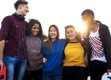 El grupo de amigos de la escuela al aire libre arma alrededor otro concepto de la unidad y de la comunidad Fotos de archivo