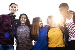El grupo de amigos de la escuela al aire libre arma alrededor otro concepto de la unidad y de la comunidad Imagenes de archivo