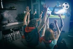 El grupo de amigos mira el juego junto en la televisi?n y disfruta imagen de archivo libre de regalías