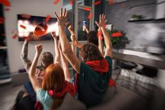 El grupo de amigos mira un partido de f?tbol junto en la televisi?n y disfruta foto de archivo libre de regalías