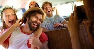 El grupo de amigos que se divierten en la furgoneta y una mujer toma imágenes almacen de video