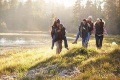 El grupo de amigos se divierte que llevan a cuestas por un lago fotografía de archivo