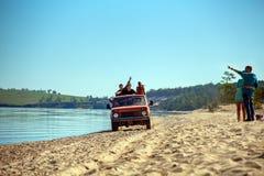 El grupo de amigos va en la orilla del lago Baikal en un coche Fotografía de archivo libre de regalías