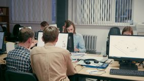 El grupo de arquitectos está trabajando en sus ordenadores en proyectos en la oficina almacen de video