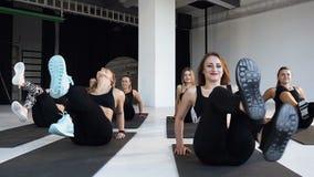 El grupo de atletas felices jovenes realiza aeróbicos de la aptitud en el piso en clase de la aptitud Concepto de yoga, aptitud,  metrajes