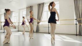 El grupo de bailarines de ballet está ensayando danza con sus movimientos practicantes del profesor y está caminando de puntillas almacen de metraje de vídeo