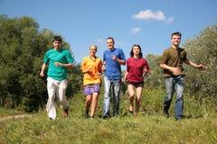 El grupo de cinco amigos en camisas multicoloras se ejecuta Foto de archivo libre de regalías