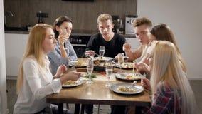 El grupo de compañeros de cuarto jovenes se está sentando en la tabla y dinning, haciendo clic por las copas de vino diciendo tos almacen de video
