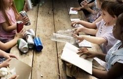 El grupo de compañeros de clase de los niños que aprenden biología recicla el ambiente imagenes de archivo