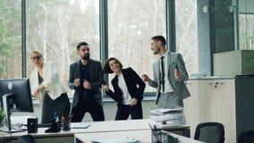 El grupo de compañeros de trabajo despreocupados felices está bailando en oficina que celebran acontecimiento de la compañía en e almacen de video