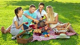Amigos que disfrutan de una comida campestre sana Foto de archivo libre de regalías