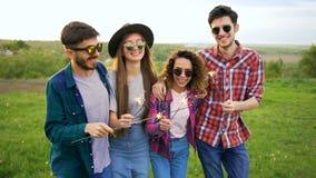 El grupo de cuatro amigos sonrientes felices camina con las bengalas en la cámara lenta Concepto del ocio del verano metrajes
