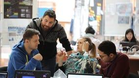 El grupo de diseñadores creativos discute proyecto de funcionamiento en oficina metrajes