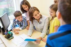 El grupo de escuela embroma con el profesor en sala de clase Imagen de archivo libre de regalías