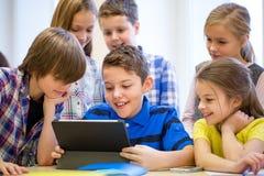 El grupo de escuela embroma con PC de la tableta en sala de clase Fotografía de archivo libre de regalías