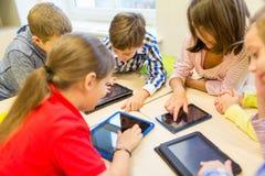 El grupo de escuela embroma con PC de la tableta en sala de clase imagenes de archivo