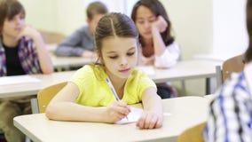 El grupo de escuela embroma la prueba de la escritura en sala de clase almacen de metraje de vídeo