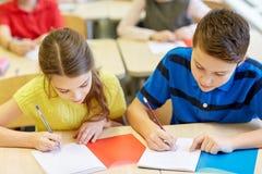 El grupo de escuela embroma la prueba de la escritura en sala de clase Foto de archivo
