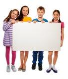 Cuatro niños que muestran al tablero con la publicidad Imagenes de archivo