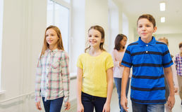 El grupo de escuela sonriente embroma caminar en pasillo Imagen de archivo