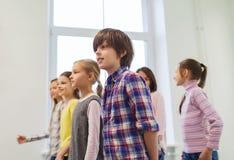 El grupo de escuela sonriente embroma caminar en pasillo Fotografía de archivo