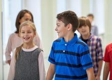 El grupo de escuela sonriente embroma caminar en pasillo Foto de archivo