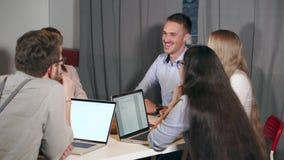 El grupo de especialistas de comercialización jovenes se está reuniendo alegre en oficina almacen de video