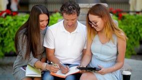 El grupo de estudiantes con las notas que se sientan en el banco al aire libre y se prepara para el examen usando la tableta negr almacen de video