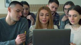 El grupo de estudiantes discute algo en el ordenador portátil metrajes
