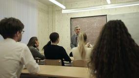 El grupo de estudiantes en una sala de clase, escuchando como su profesor lleva a cabo una conferencia metrajes